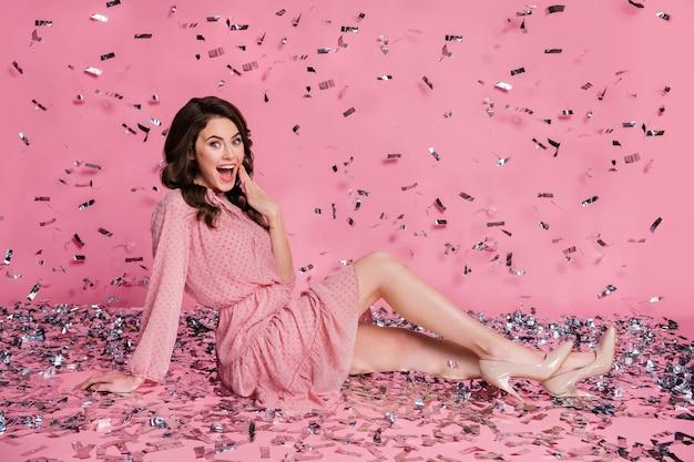 Portrait de belle fille joyeuse étonnée assise s'amusant à voler des confettis