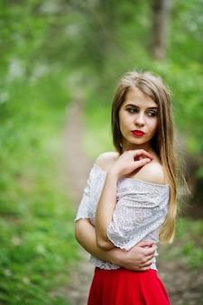 Portrait de belle fille avec des lèvres rouges au jardin de fleurs de printemps, porter sur la robe rouge et le chemisier blanc.