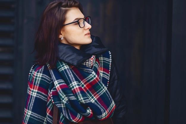 Portrait de belle fille à lunettes et une écharpe contre un mur en bois