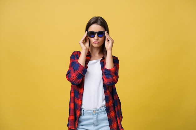 Portrait d'une belle fille à lunettes rondes sur fond jaune dans le studio.