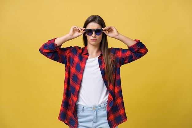 Portrait d'une belle fille à lunettes rondes sur fond jaune en studio.