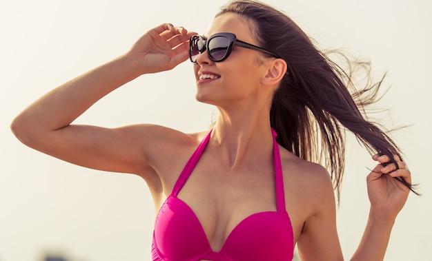 Portrait de belle fille en maillot de bain rose et lunettes de soleil.