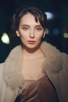 Portrait de belle fille en manteau avec col en fourrure posant dans une pièce sombre avec des lumières allumées