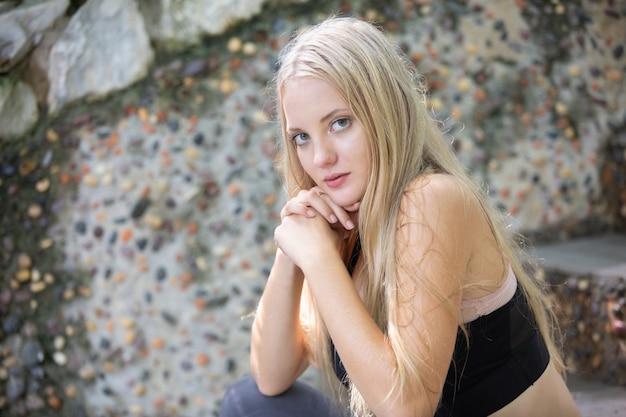Portrait d'une belle fille de mode aux cheveux blonds en tenue de sport posant en plein air