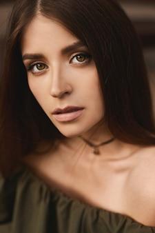 Portrait de belle fille modèle brune aux yeux verts profonds et avec un maquillage doux en robe vert foncé à la mode avec des épaules nues