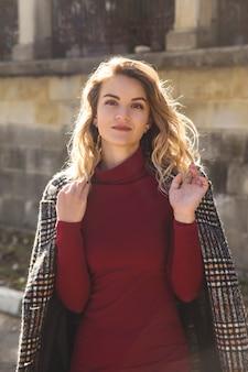 Portrait d'une belle fille moderne avec des cheveux blonds ondulés en manteau d'automne au soleil.