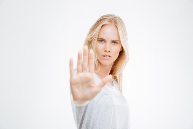 Portrait d'une belle fille montrant un panneau d'arrêt avec palmier isolé sur un mur blanc