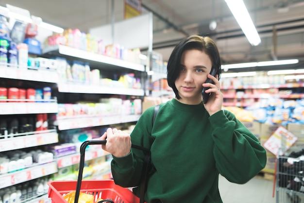 Portrait d'une belle fille parlant au téléphone lors de ses achats dans un supermarché.