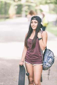 Portrait d'une belle fille de patineur au parc.