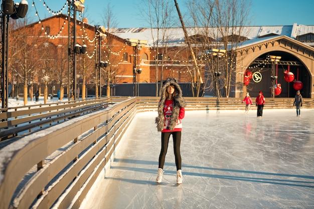 Portrait d'une belle fille à la patinoire en hiver