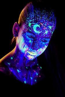 Portrait de belle fille avec de la peinture ultraviolette sur son visage. fille avec maquillage néon à la lumière de couleur.