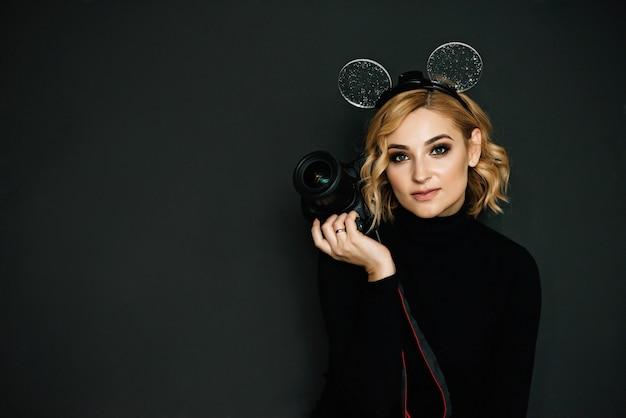 Portrait d'une belle fille photographe blonde avec un appareil photo en mains