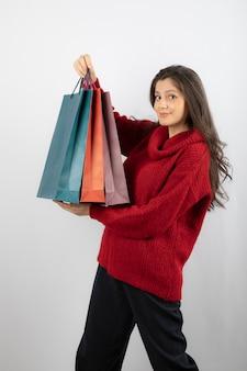 Portrait d'une belle fille portant un pull tenant des sacs à provisions isolés sur un mur blanc.