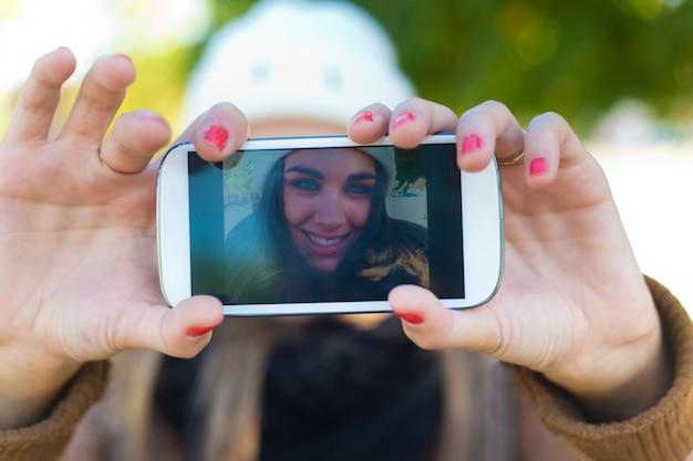 Portrait d'une belle fille prenant une selfie avec un téléphone portable dans