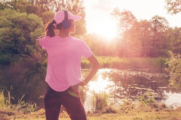 Portrait d'une belle fille qui court dans un parc ensoleillé au casque avec un smartphone. concept d'applications musicales. technique mixte