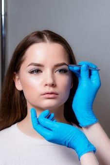 Portrait d'une belle fille, qui peignent les sourcils.