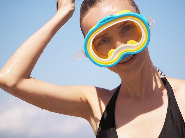 Portrait d'une belle fille qui rit sur la plage après la plongée en apnée