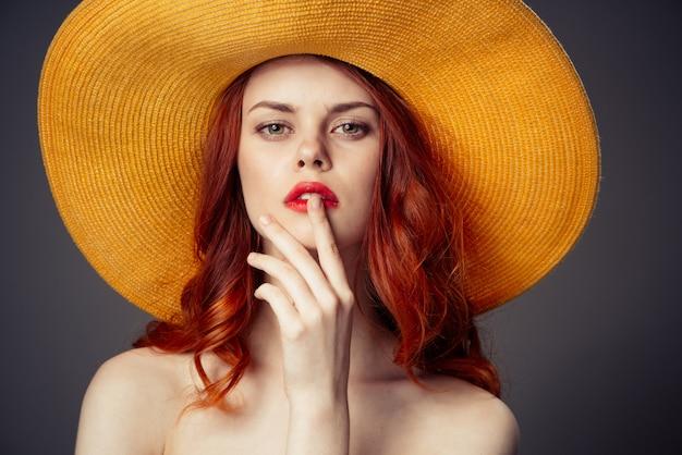 Portrait d'une belle fille rousse dans un chapeau orange, studio
