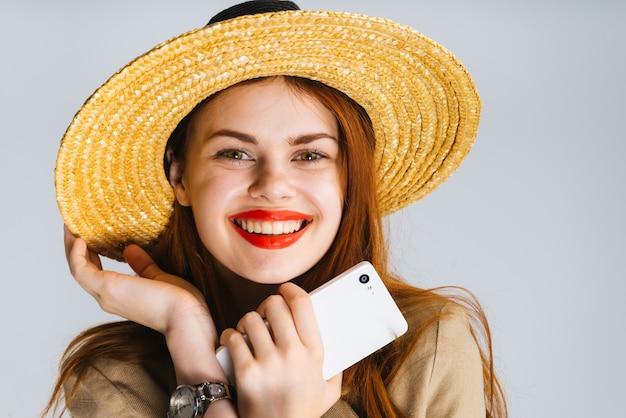 Portrait d'une belle fille rousse dans un chapeau de paille, elle sourit en regardant la caméra. isolé sur un fond gris