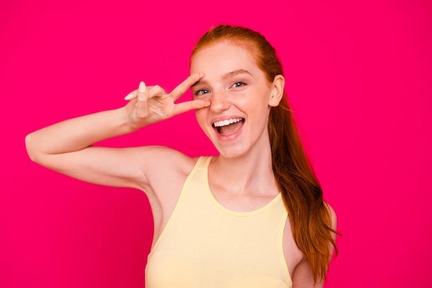 Portrait belle fille rousse isolée sur mur rose