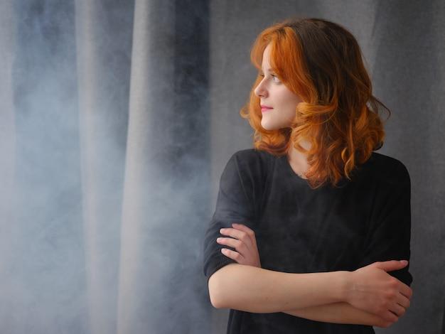 Portrait d'une belle fille rousse avec lumière naturelle et fumée