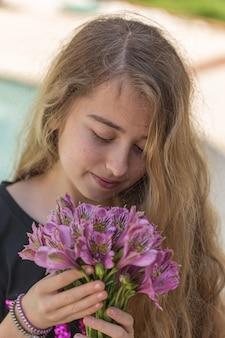 Portrait de belle fille sentant les fleurs à l'extérieur en t-shirt noir pendant la journée.