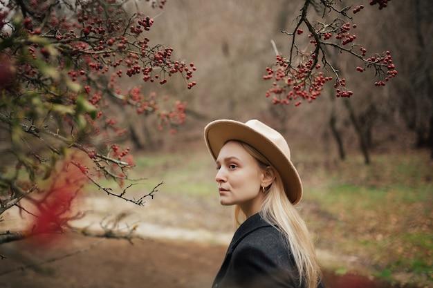 Portrait de belle fille sérieuse avec chapeau posant sur le fond d'un arbre aux fruits rouges.