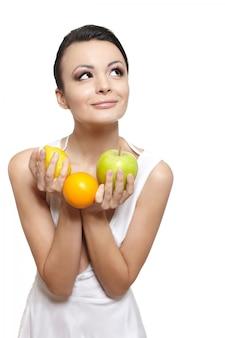 Portrait de la belle fille souriante heureuse avec des fruits citron et pomme verte et orange isolé sur blanc