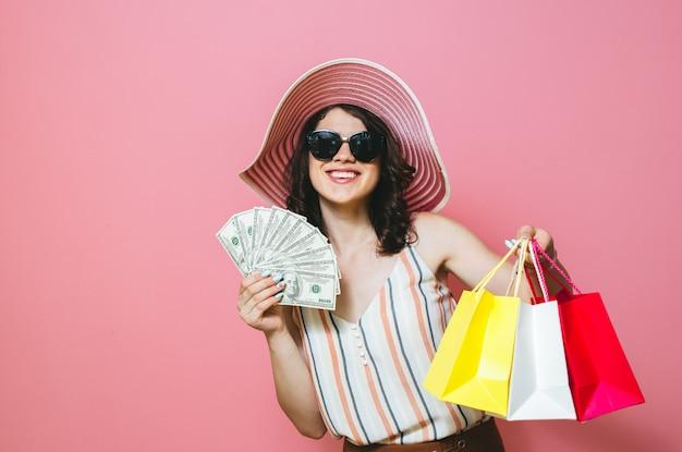 Portrait d'une belle fille souriante avec des lunettes de soleil, tenant des sacs à provisions et des billets en argent sur fond rose