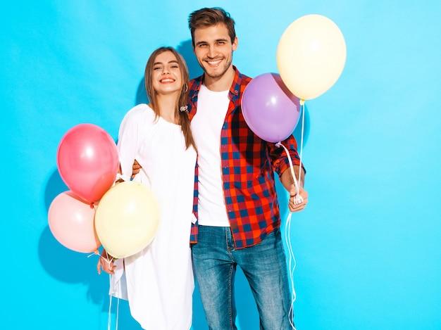 Portrait de belle fille souriante et son beau petit ami tenant des tas de ballons colorés et riant. bon anniversaire