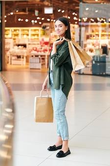 Portrait de belle fille souriante en tenue décontractée debout avec des sacs à provisions en centre commercial