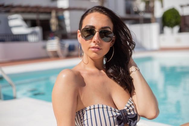 Portrait d'une belle fille en train de bronzer au bord de la piscine avec des lunettes de soleil