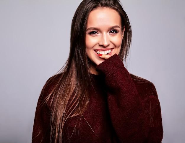 Portrait de la belle heureuse femme brune mignonne modèle dans des vêtements de chandail rouge chaud décontracté isolé sur gris avec du maquillage de soirée et des lèvres colorées