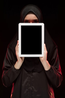 Portrait de belle intelligente jeune femme musulmane portant le hijab noir, tenant la tablette
