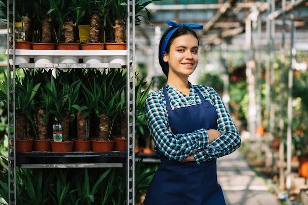 Portrait d'une belle jardinière féminine debout dans une serre