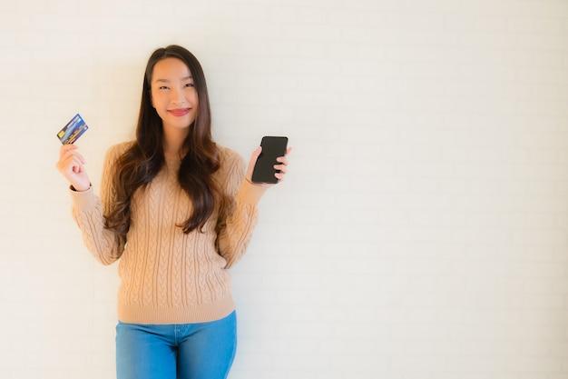 Portrait belle jeune asiatique utilise un téléphone intelligent mobile avec carte de crédit