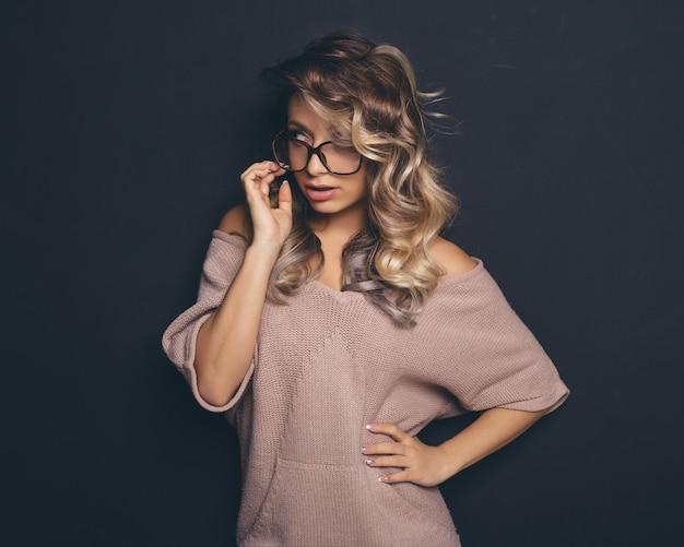 Portrait d'une belle jeune blonde portant des lunettes à la mode et des vêtements décontractés et posant sur fond noir