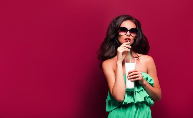 Portrait de la belle jeune brune à lunettes de soleil et robe verte avec cocktail sur une scène rouge. isolé