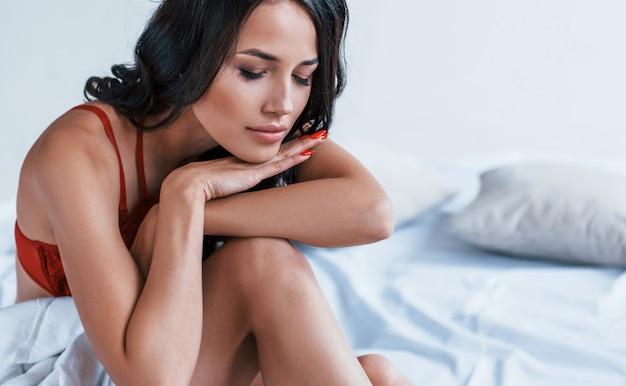 Portrait de la belle jeune brune qui est en sous-vêtements rouges assis sur le lit.