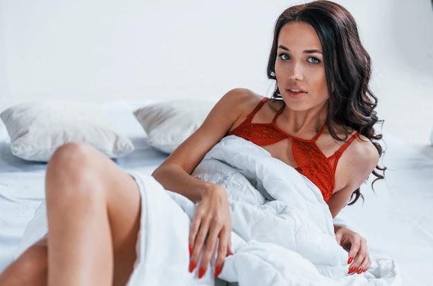 Portrait de la belle jeune brune qui est en sous-vêtements rouges dans une pièce blanche allongée sur le lit avec une couverture.