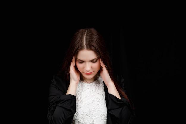 Portrait de la belle jeune brune se sentant stressée ou mal de tête