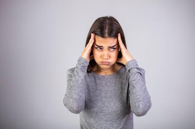 Portrait de la belle jeune brune touchant ses tempes ressentant du stress, sur fond gris.