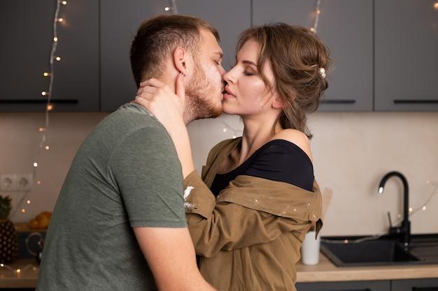 Portrait de la belle jeune couple dans des vêtements décontractés s'embrasser et souriant