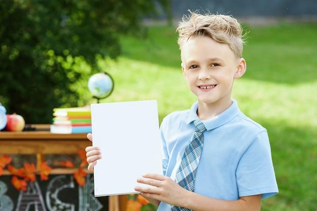 Portrait d'une belle jeune écolière debout avec des livres