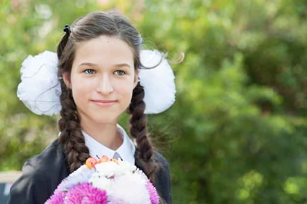 Portrait d'une belle jeune écolière avec une pomme rouge sur des livres dans un uniforme d'école de fête