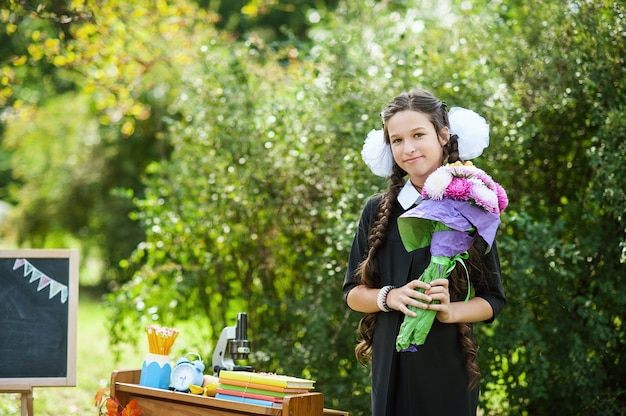 Portrait d'une belle jeune écolière en uniforme d'école de fête