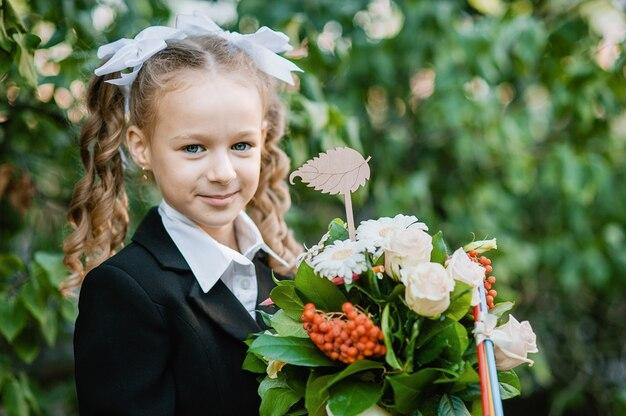 Portrait d'une belle jeune élève de première année avec une pomme rouge sur des livres dans un uniforme d'école de fête