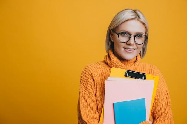 Portrait d'une belle jeune étudiante blonde habillée en jaune regardant la caméra en souriant tout en tenant ses livres sur fond jaune.