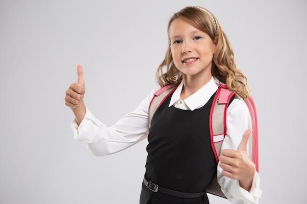 Portrait d'une belle jeune étudiante expressive qui montre les pouces vers le haut