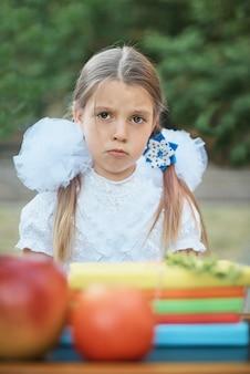 Portrait d'une belle jeune étudiante de première année assise à un bureau dans le parc d'automne de fond.